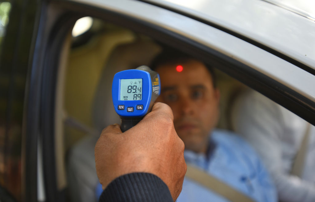 A security guard holds up an infrared thermometer to screen passengers in a car, as a precautionary measure against coronavirus (COVID-19), at Barakhamba Road on March 9, 2020 in New Delhi, India.