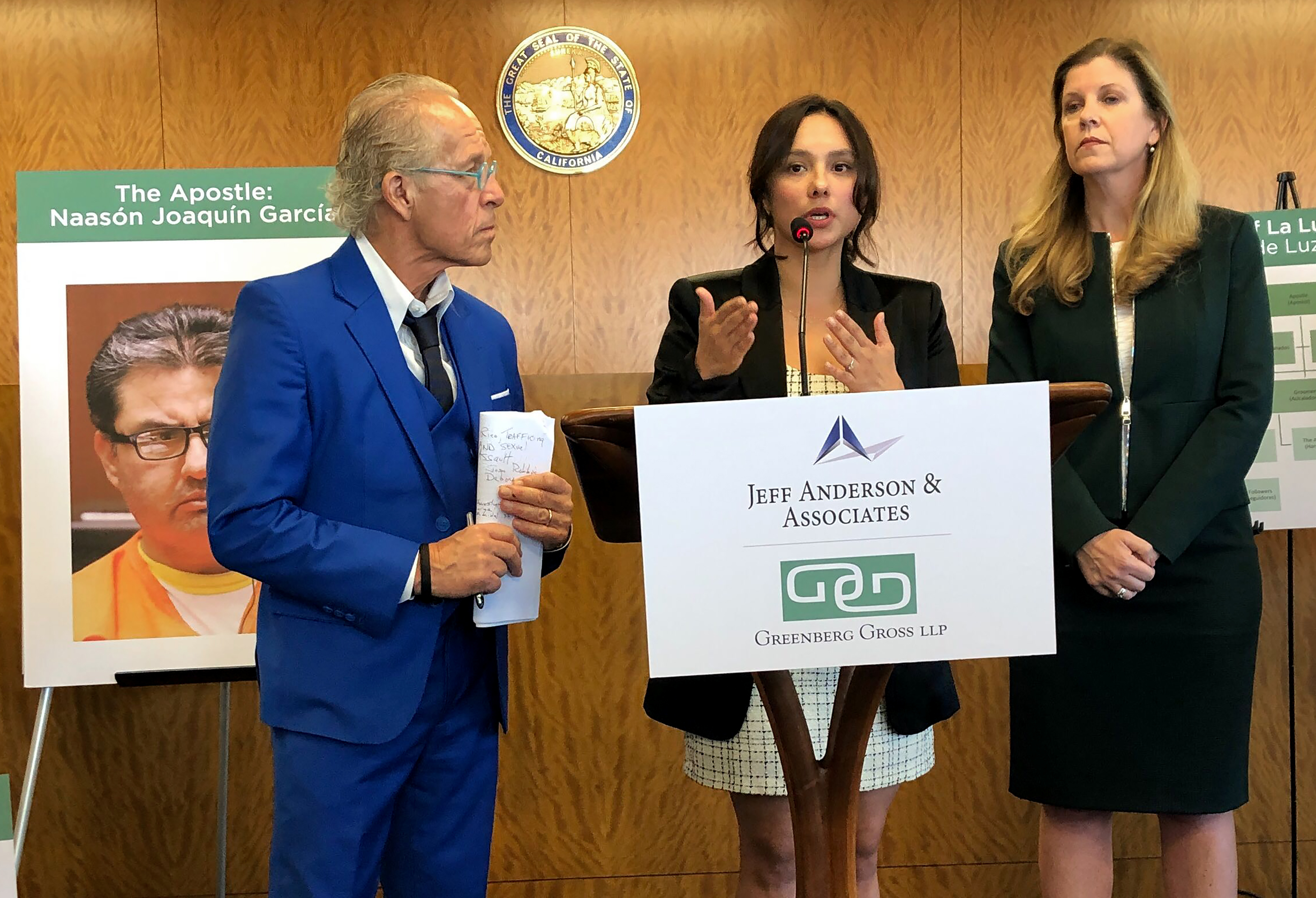 Sochil Martin, center, with lawyers Jeff Anderson, left, and Deborah Mallgrave, speaks at a news conference in Los Angeles on Feb. 13, 2020.