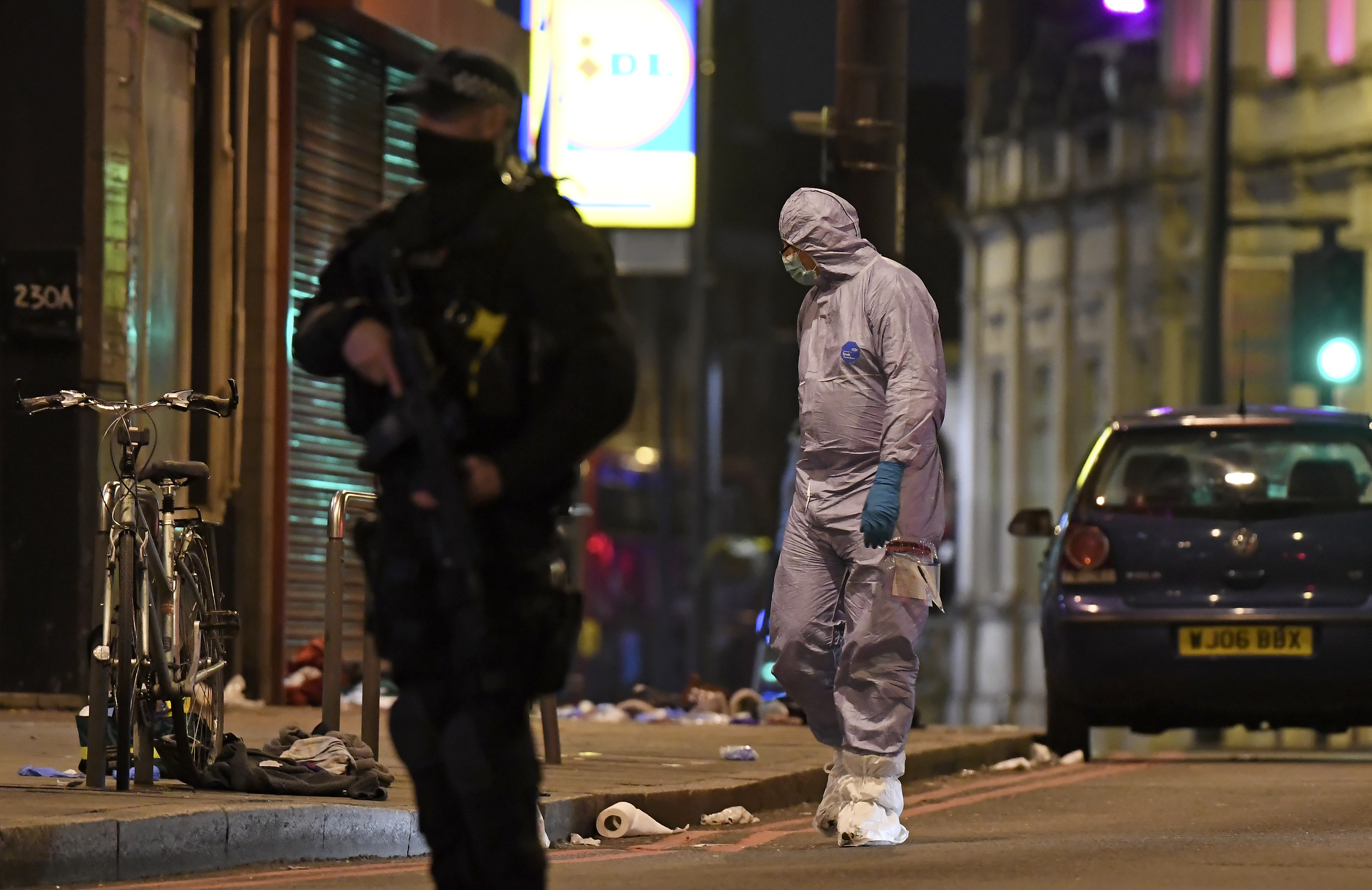 A police forensic officer looks around near the scene after a stabbing incident in Streatham London, England, Sunday, Feb. 2, 2020. London police officers shot and killed a suspect after at least two people were stabbed Sunday in what authorities are investigating as a terror attack.