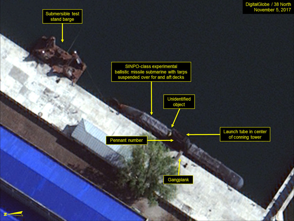 This 2017 satellite image shows a suspected North Korean SINPO-class submarine and submersible test stand barge berthed in the secure boat basin.