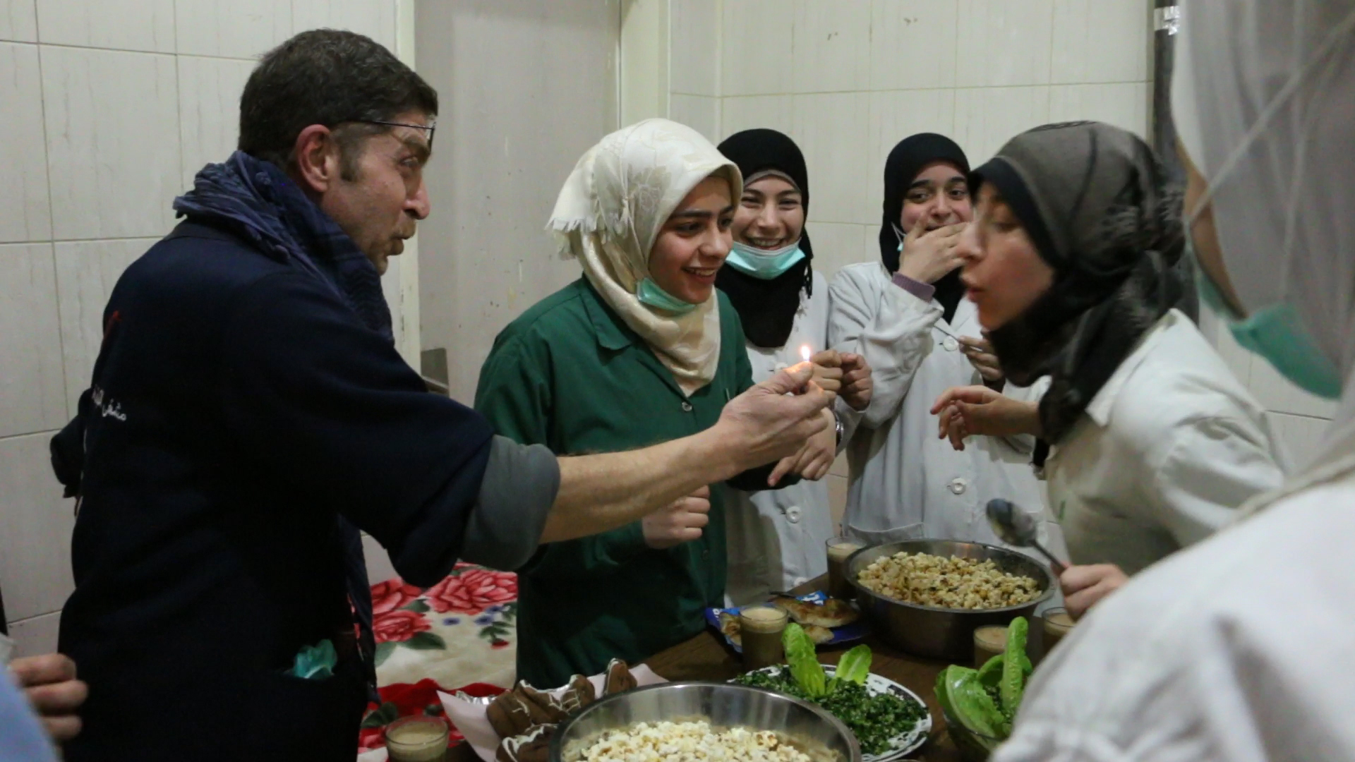 Al Ghouta, Syria - Dr Salim (L) holds a light for Amani (R) to blow out during her birthday celebration in the hospital.