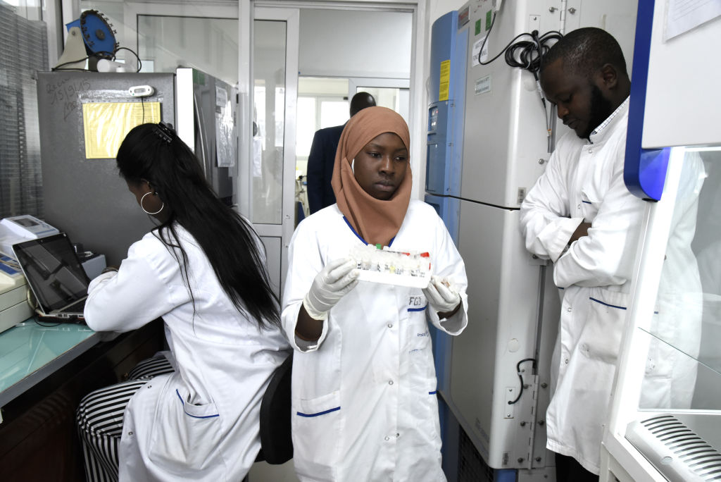 Scientific staff members works in a secure laboratory, researching the new coronavirus, at the Pasteur Institute in Dakar on Feb. 3, 2020.