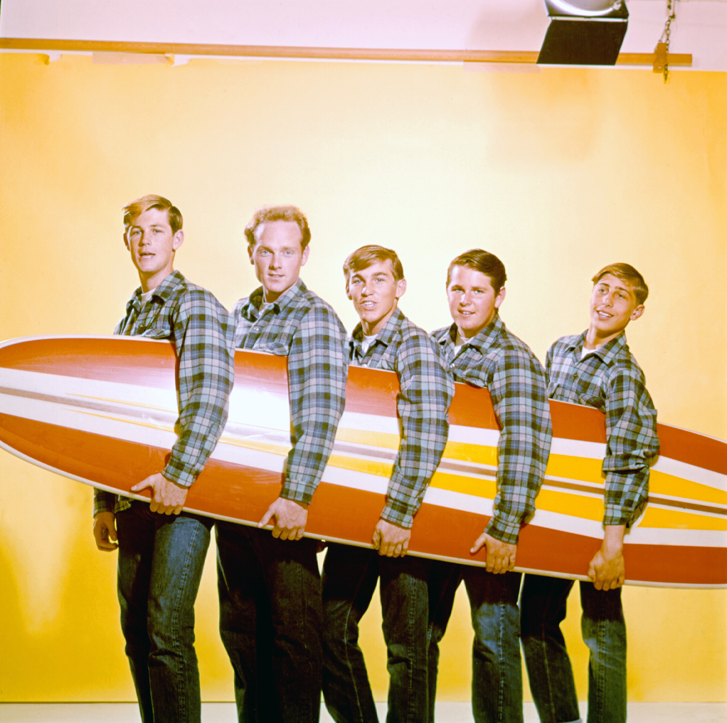 Rock and roll band  The Beach Boys  pose for a portrait with a surfboard in August 1962 in Los Angeles. L—R: Brian Wilson, Mike Love,  Dennis Wilson, Carl Wilson, David Marks.