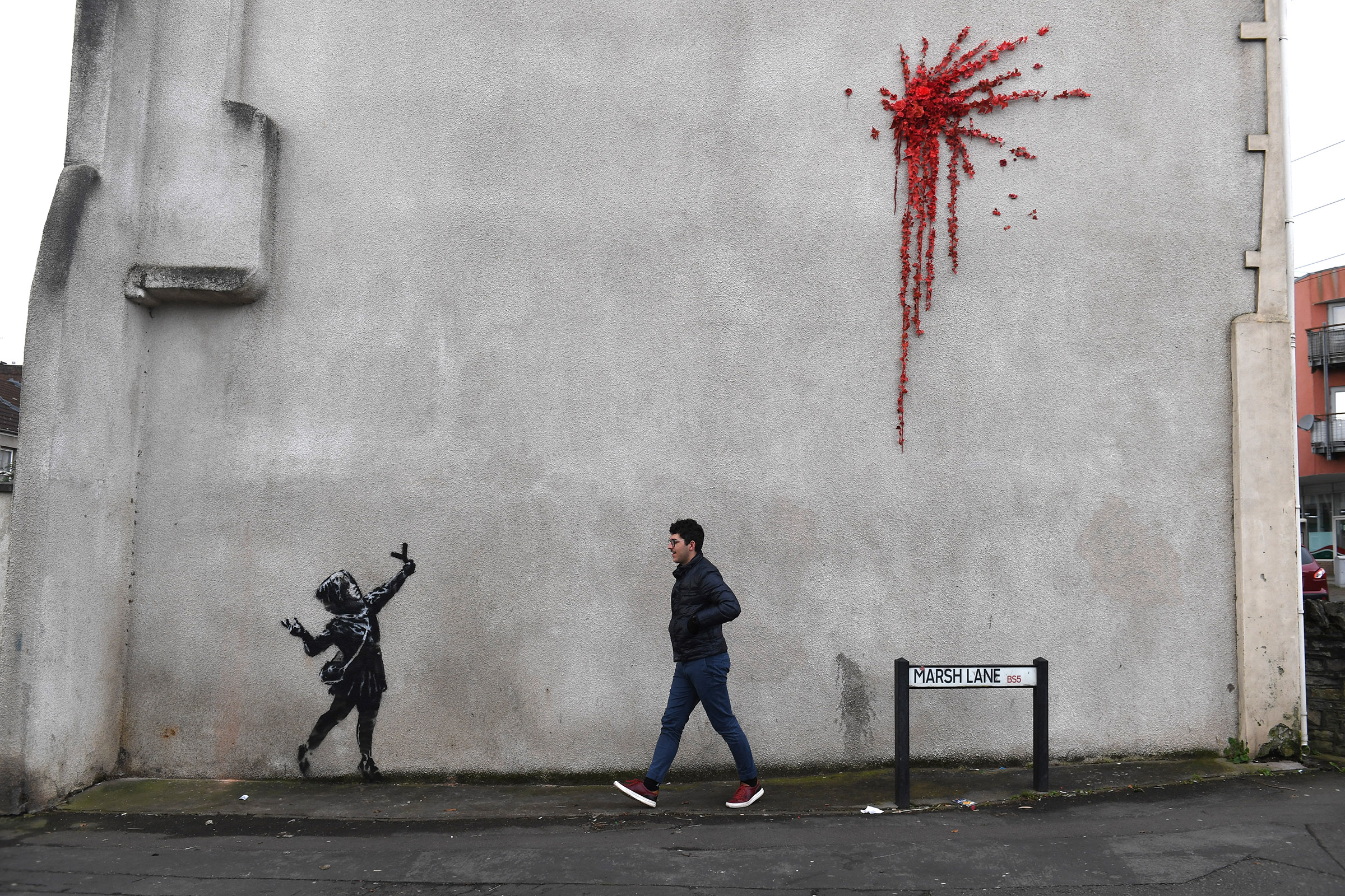 A member of the public walks past the new Banksy art in Bristol, England on Feb. 14, 2020.