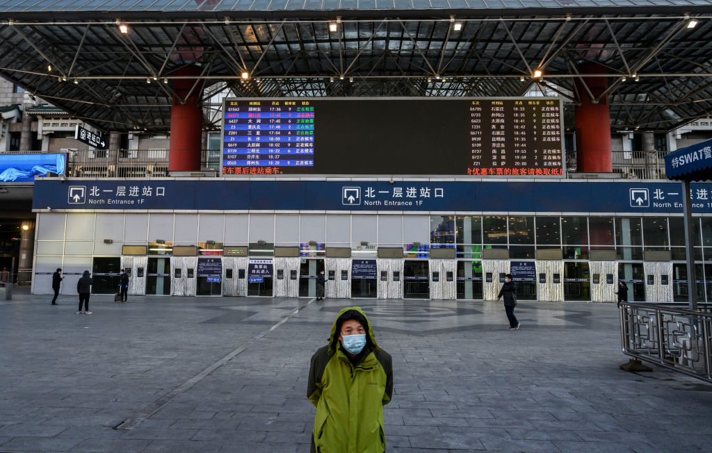 A Chinese man wears a protective mask as he stands outside a main entrance at Beijing West Railway Station as it is nearly empty on February 16, 2020 in Beijing, China.