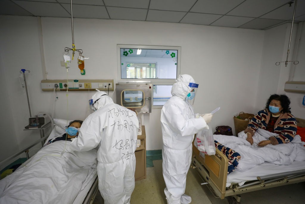 Two medical personnel work in the patients' ward in Jinyintan Hospital, designated for critical COVID-19 patients, in Wuhan in central China's Hubei province on Feb. 13, 2020.