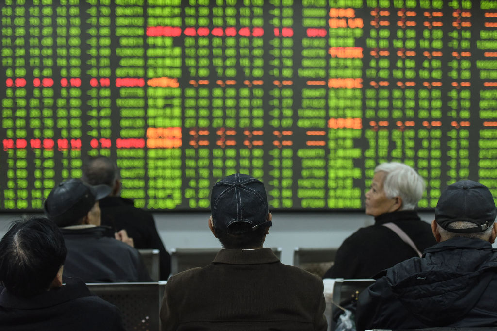 Investors look at a screen showing stock market movements at a securities company in Hangzhou in China's eastern Zhejiang province on Feb. 3, 2020.