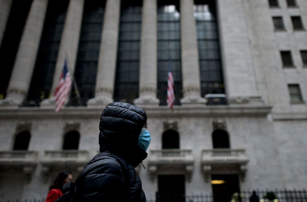 A woman with a facial mask passes the New York Stock Exchange on Feb. 3, 2020.