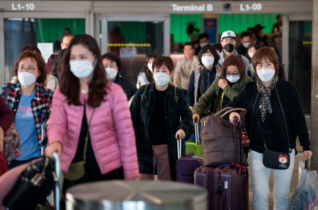 Passengers wear protective masks to protect against the spread of the Coronavirus as they arrive on a flight from Asia at the Los Angeles International Airport, California, on January 29, 2020.