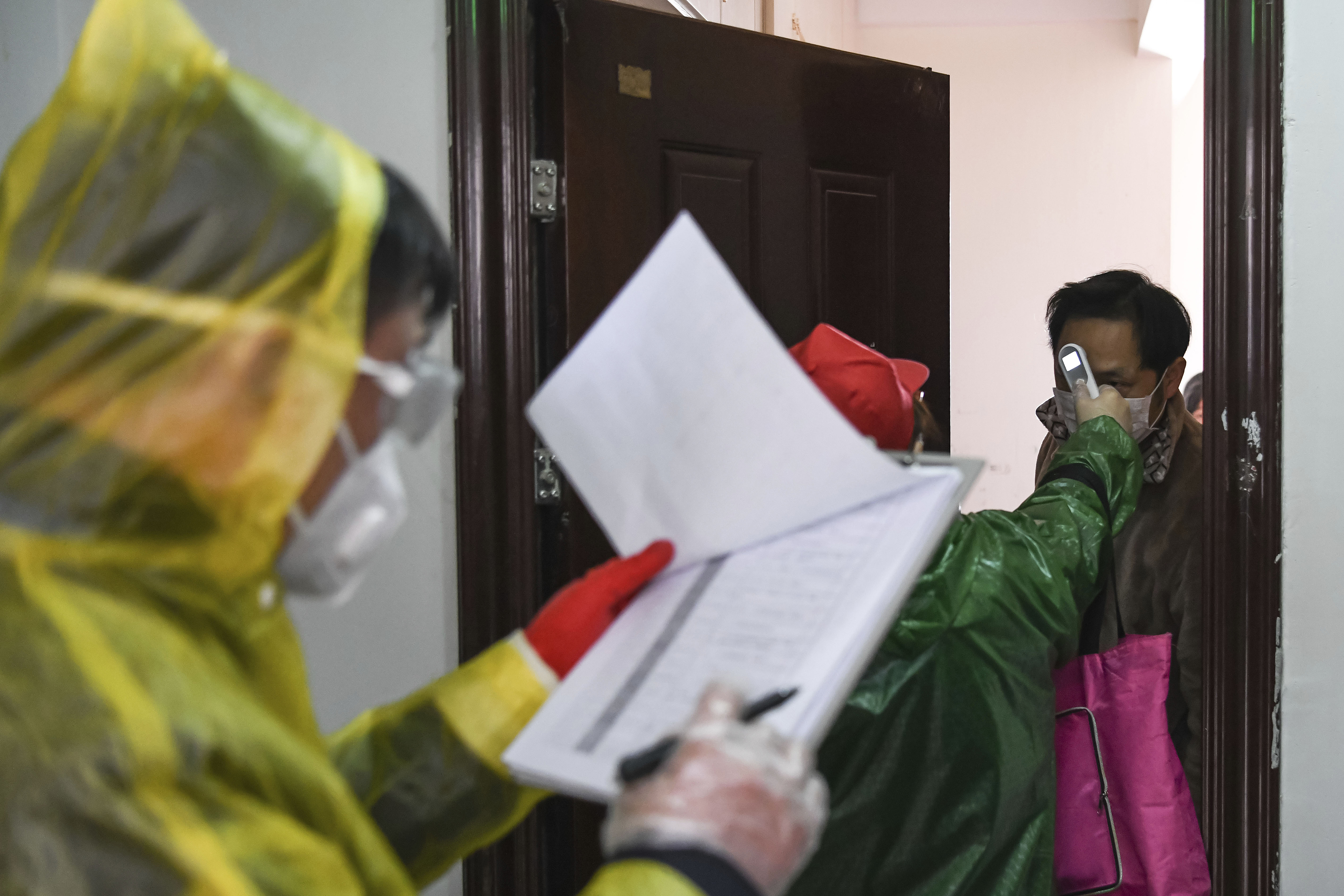 In this photo released by Xinhua News Agency, workers go door to door to check the temperature of residents during a health screening campaign in the Qingheju Community, Qingshan District of Wuhan in central China's Hubei Province on Feb. 18, 2020.