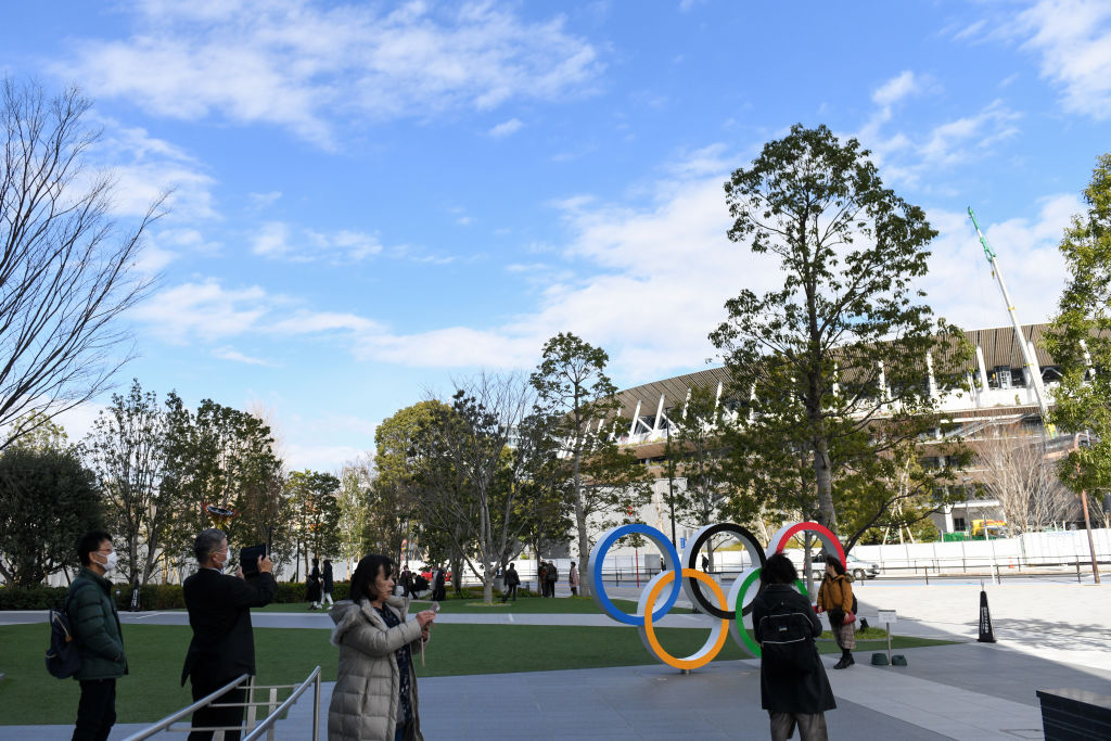 People take pictures of the Olympic rings installed near the New National Stadium, the main venue for the Tokyo 2020 Olympic and Paralympic Games, back, in Tokyo, Japan, on Wednesday, Feb. 19, 2020.