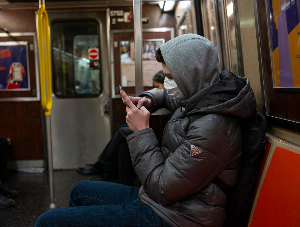 A man riding the New York City subway wears a medical face mask out of concern over the coronavirus on Feb. 2, 2020.