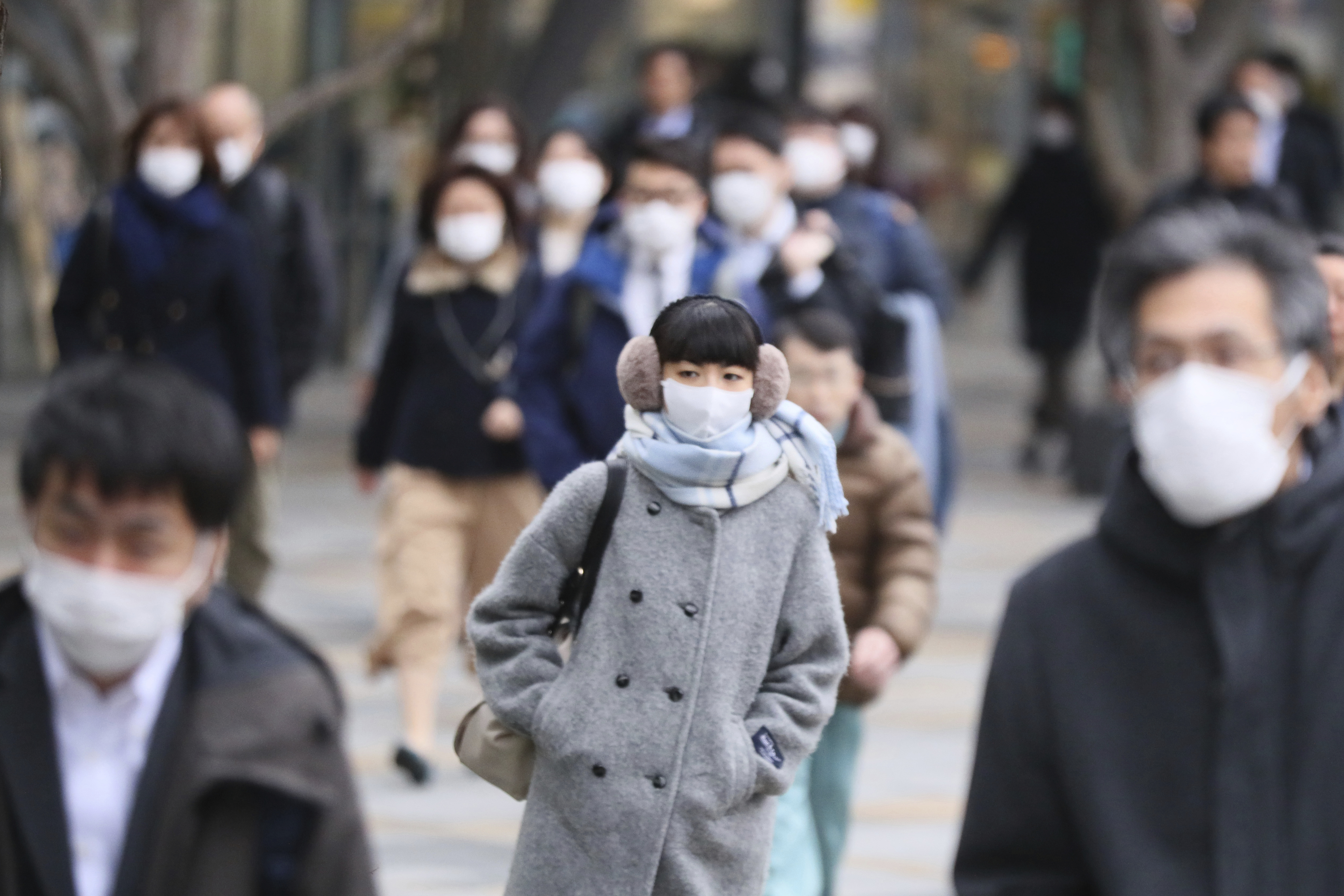 People wearing mask head for their offices and others in Tokyo on Feb. 26, 2020.