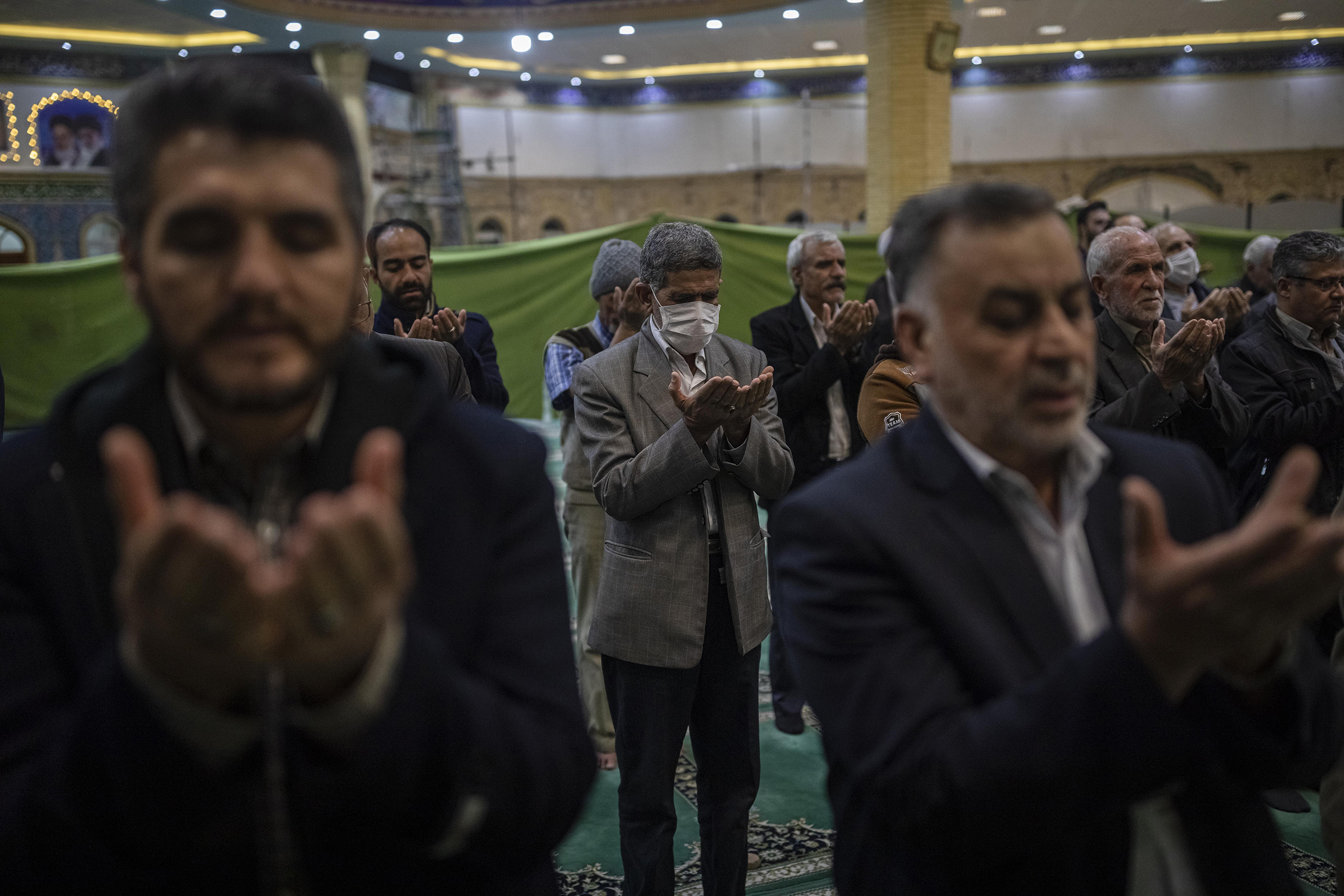 Iranian men are praying with or without a protective face mask in a mosque in Arak, capital of Markazi Province