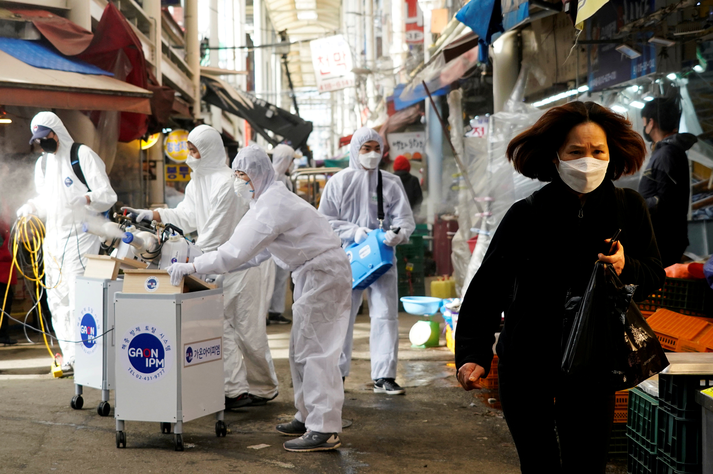 A woman wearing a mask to prevent contracting the coronavirus reacts as employees from a disinfection service company sanitize a traditional market in Seoul on Feb. 26