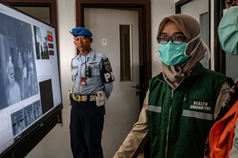 An Indonesian health official monitors as passengers from an international flight pass a thermal scanner upon arrival at the Adisucipto International Airport in Yogyakarta, Indonesia on Jan. 23, 2020.