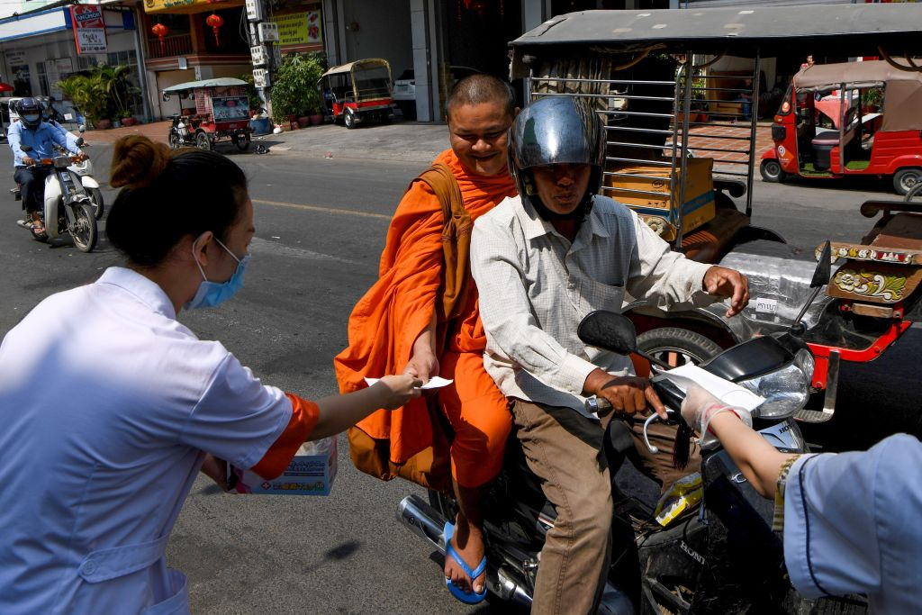 Volunteers hand out free face masks to people along a street in Phnom Penh, Cambodia on Jan. 29, 2020.