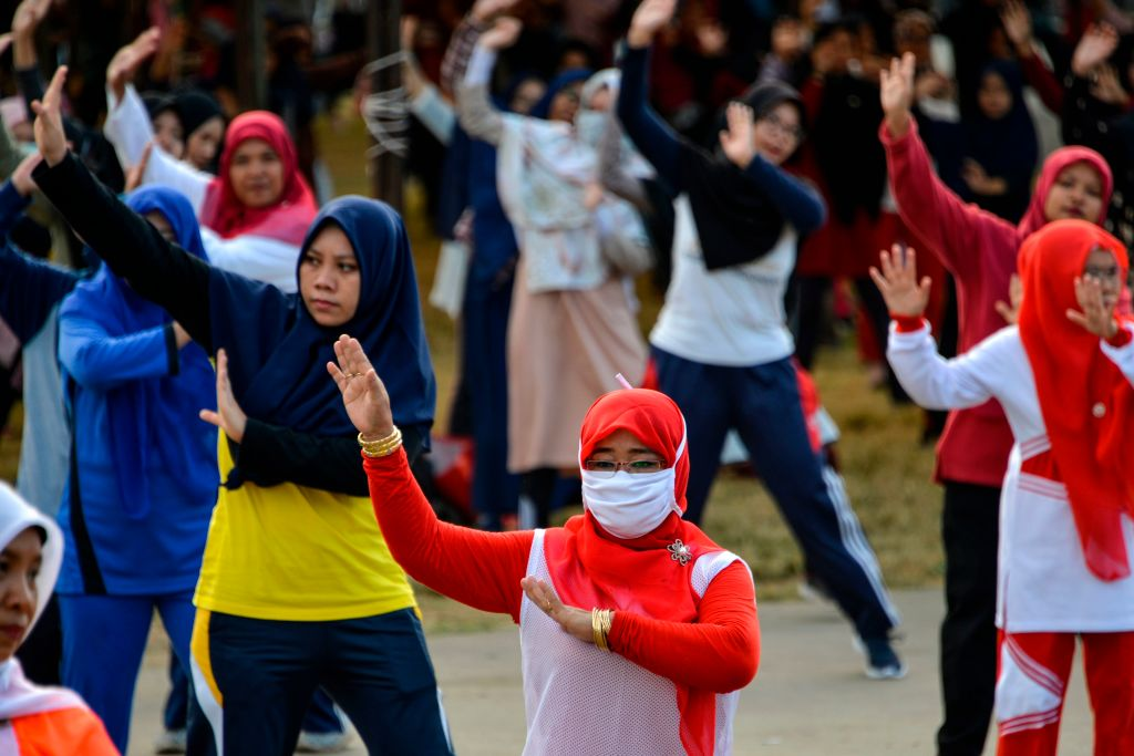 Women wearing face masks exercise at a playground in Banda Aceh, Indonesia on Feb. 2, 2020.