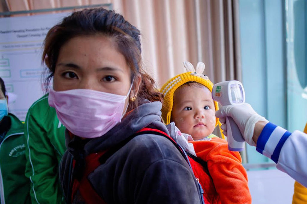 A Myanmar health officer checks the temperature of a child entering the Myanmar-China border crossing in Muse, Shan State on Jan. 31, 2020.