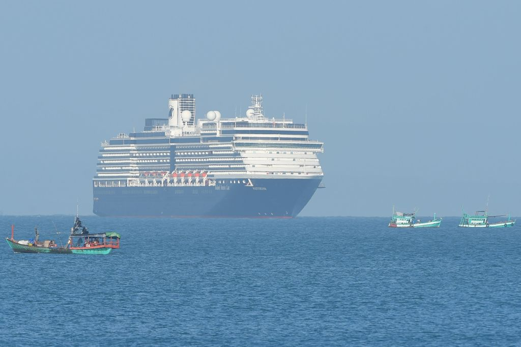 The Westerdam cruise ship is seen past fishing boats as it approaches a port in Sihanoukville, Cambodia, on Feb. 13, 2020.