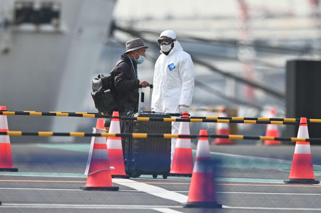 A passenger wearing a face mask gets off the Diamond Princess cruise ship in Yokohama, Japan on Feb. 20, 2020.
