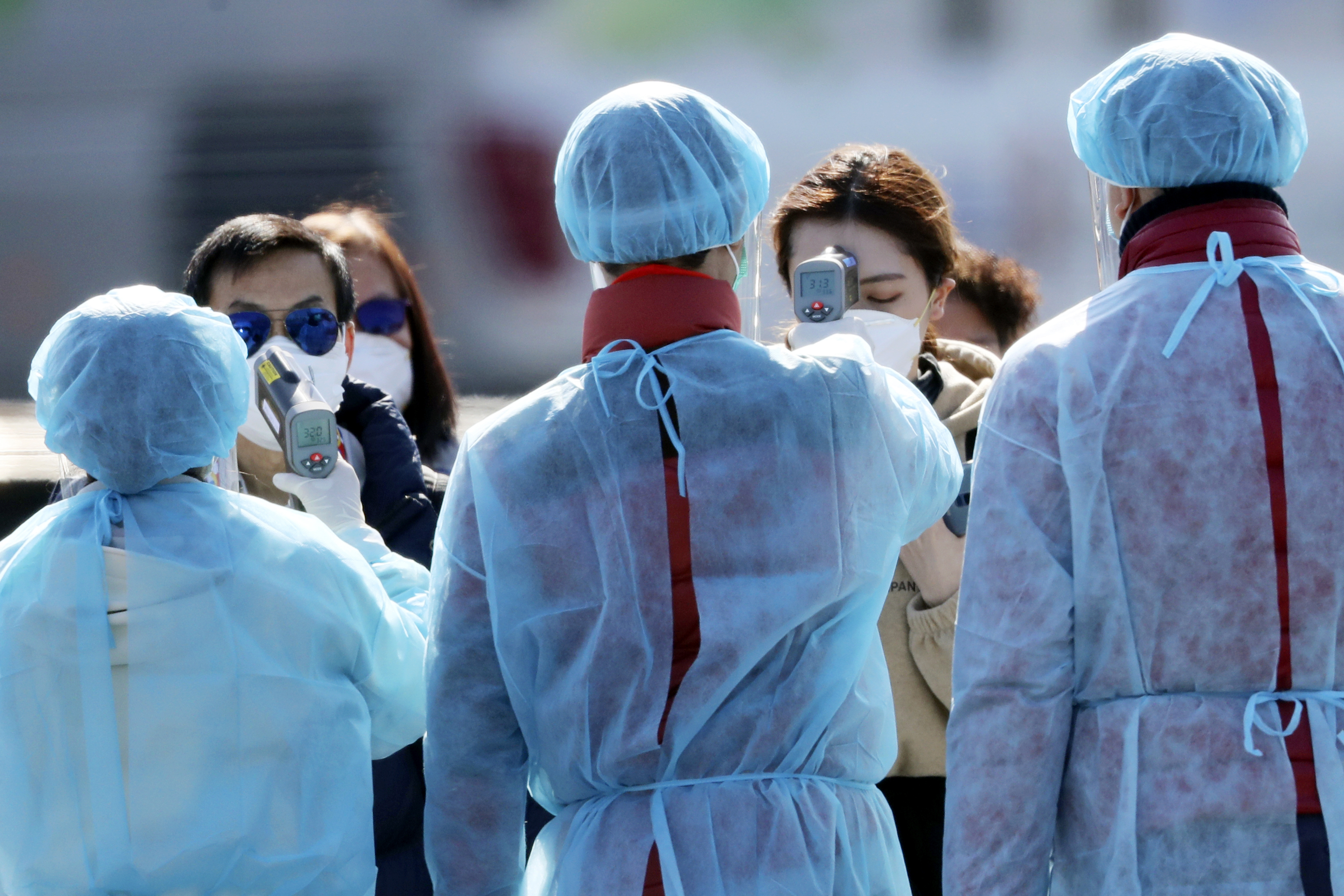 Officials in protective suits check the temperature of Diamond Princess cruise passengers before they board at a port in Yokohama, Japan, on Feb. 21, 2020.
