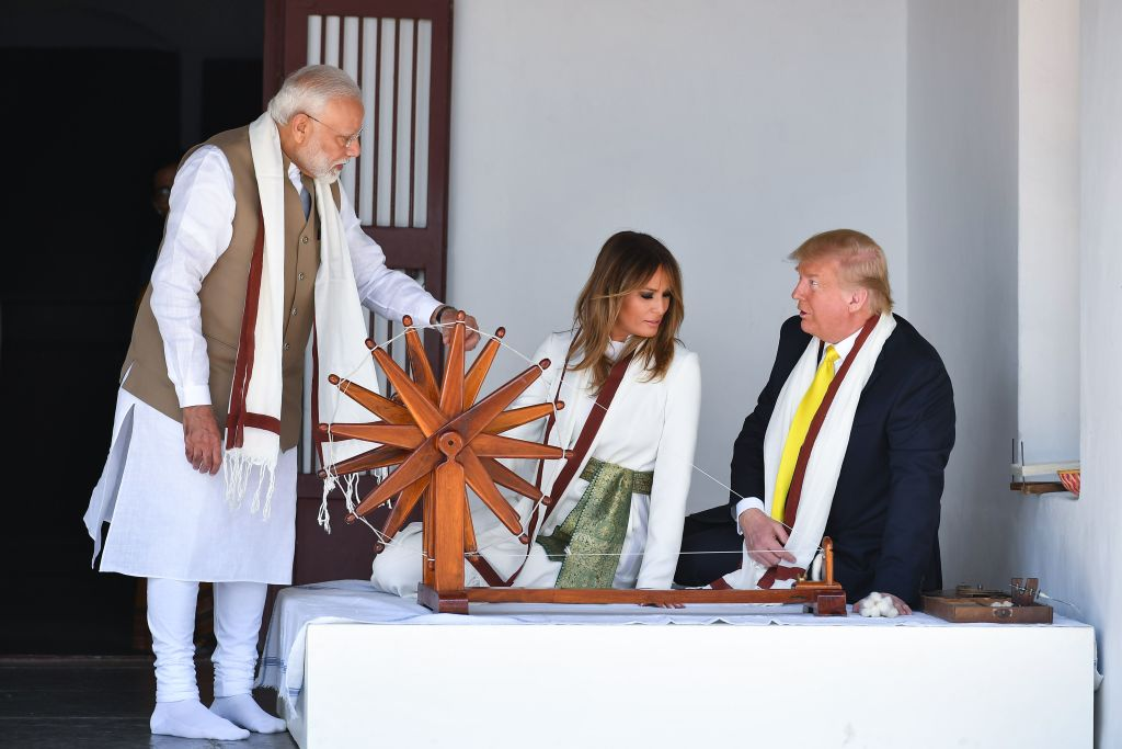 President Donald Trump and First Lady Melania Trump listen to India's Prime Minister Narendra Modi as they sit next to a charkha, or spinning wheel, during their visit at Gandhi Ashram in Ahmedabad on Feb. 24, 2020.