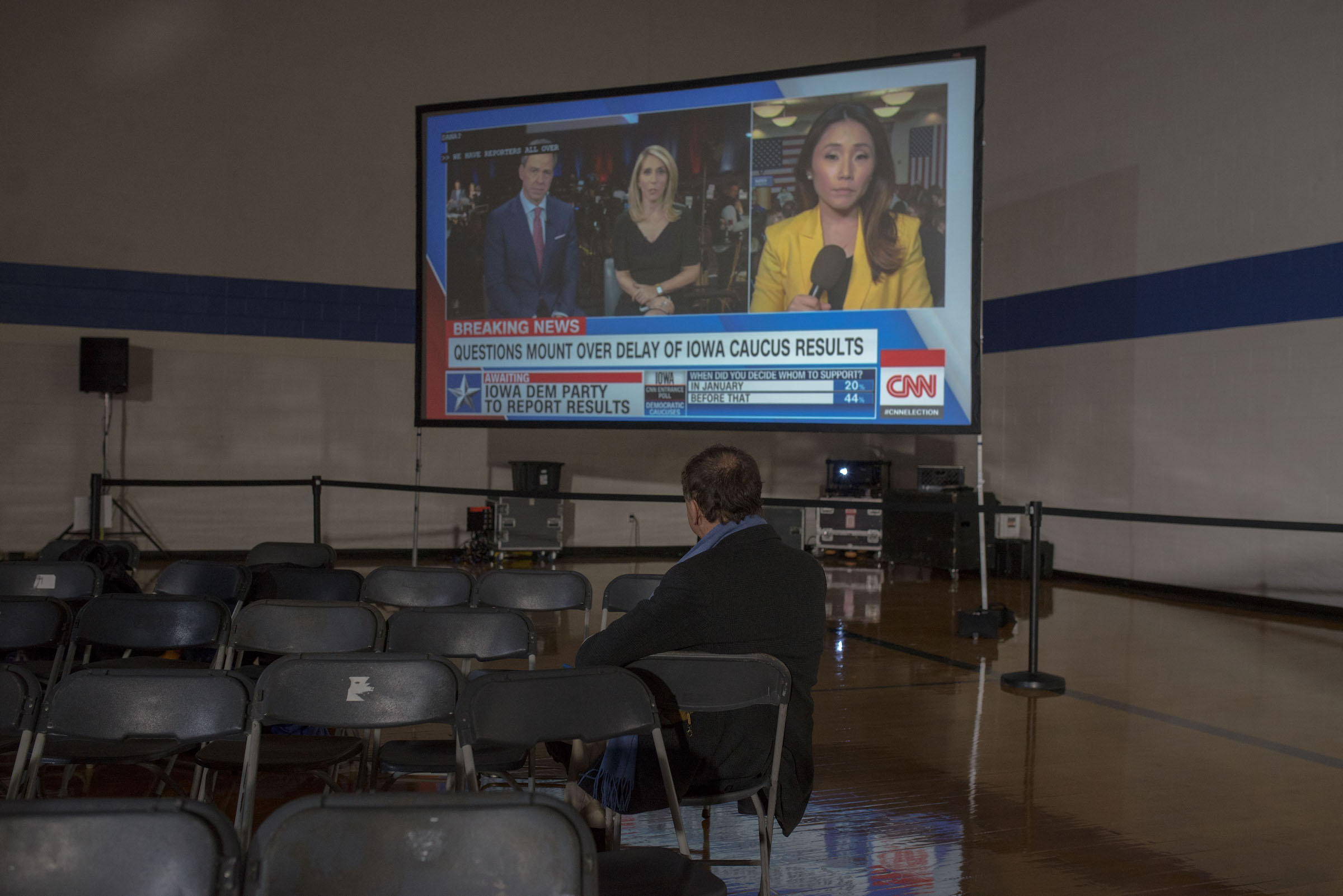 An attendee at an Iowa Caucus watches the news on Caucus Day in Des Moines, Iowa on Feb. 3, 2020.