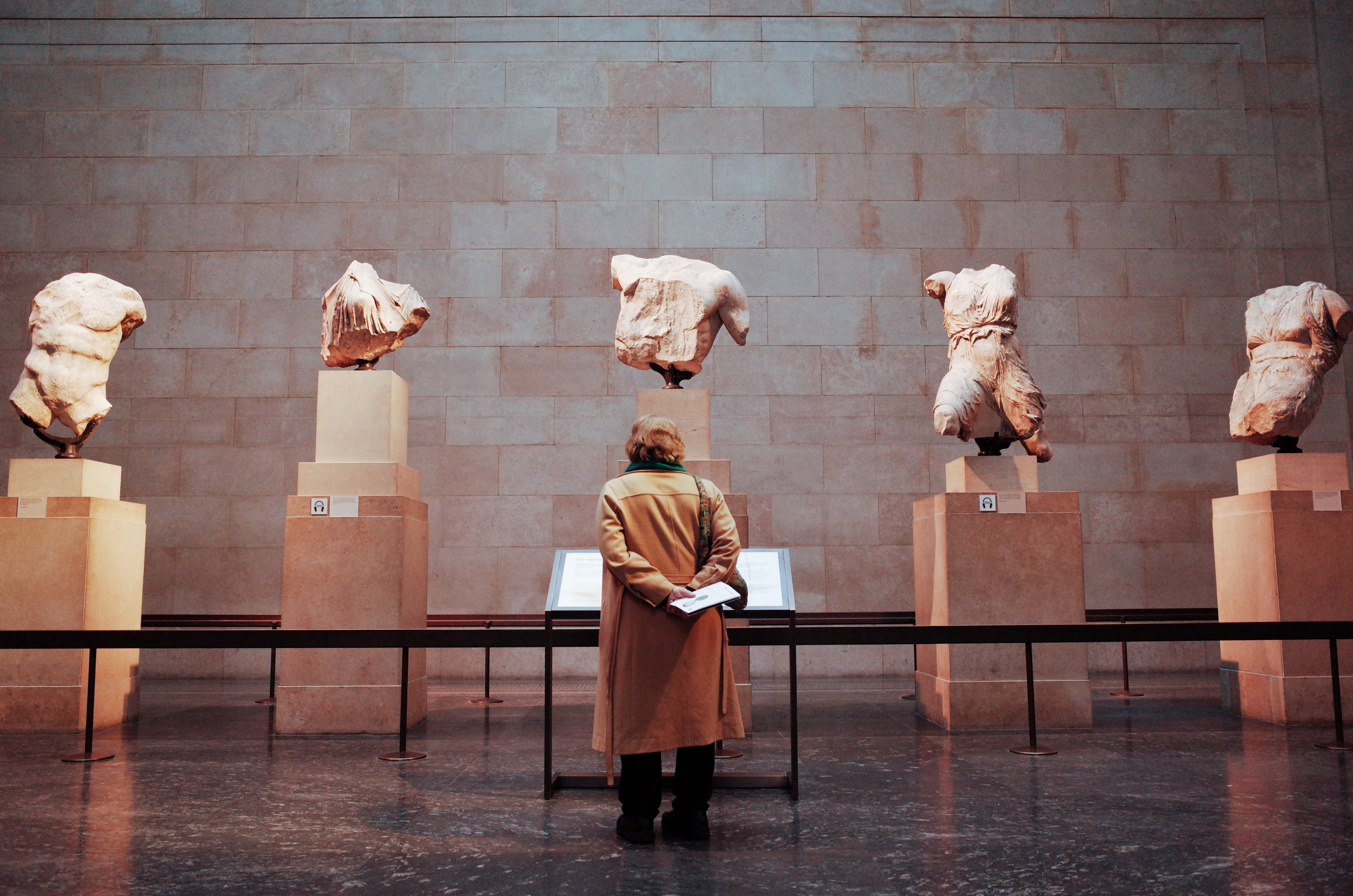 A woman looks at a section of the Parthenon Sculptures exhibit in the British Museum in London, England, on February 13, 2020.
