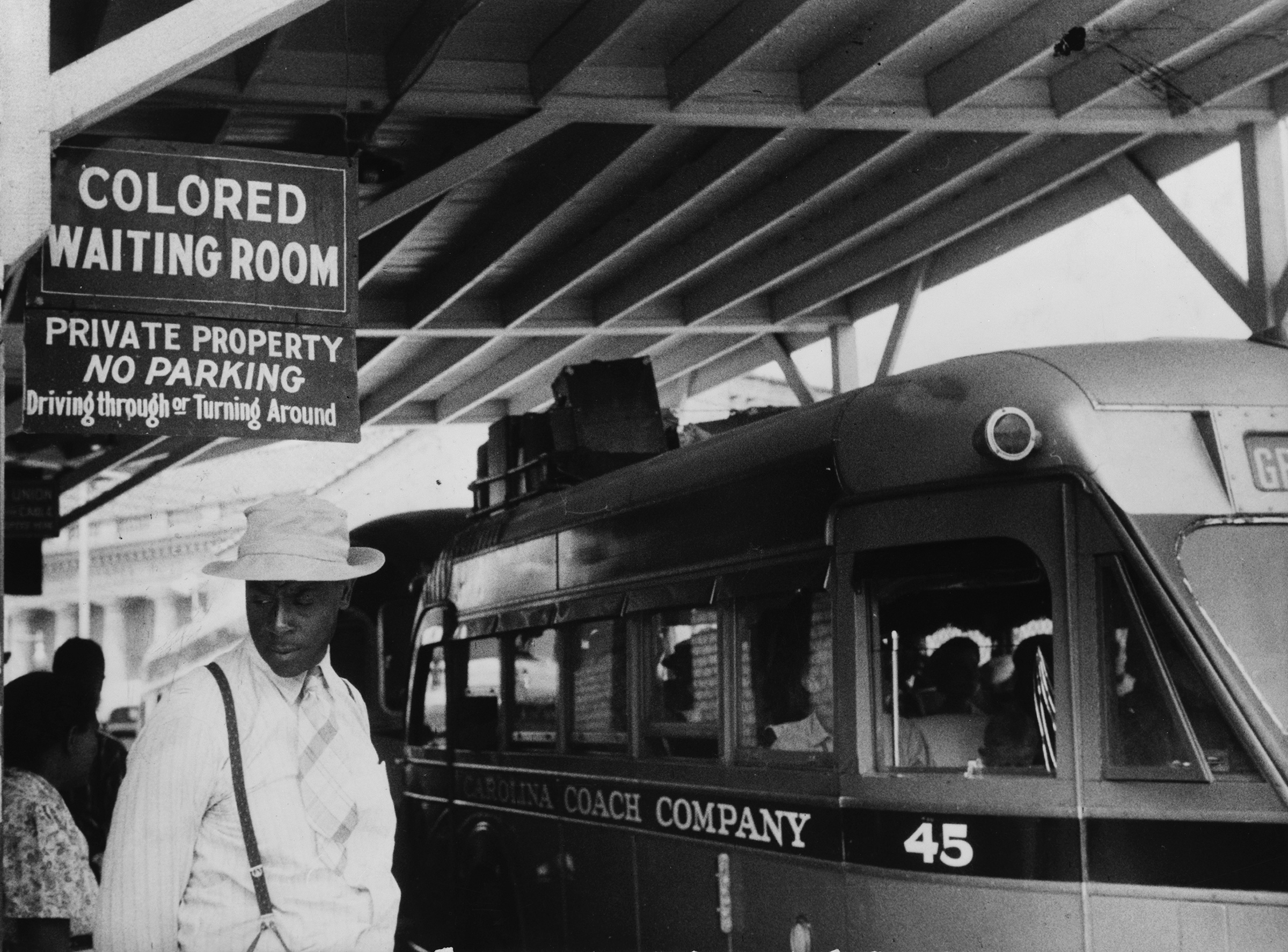 "Passengers under a sign that reads ""Colored Waiting Room"" at a bus station in Durham, N.C., in 1940"