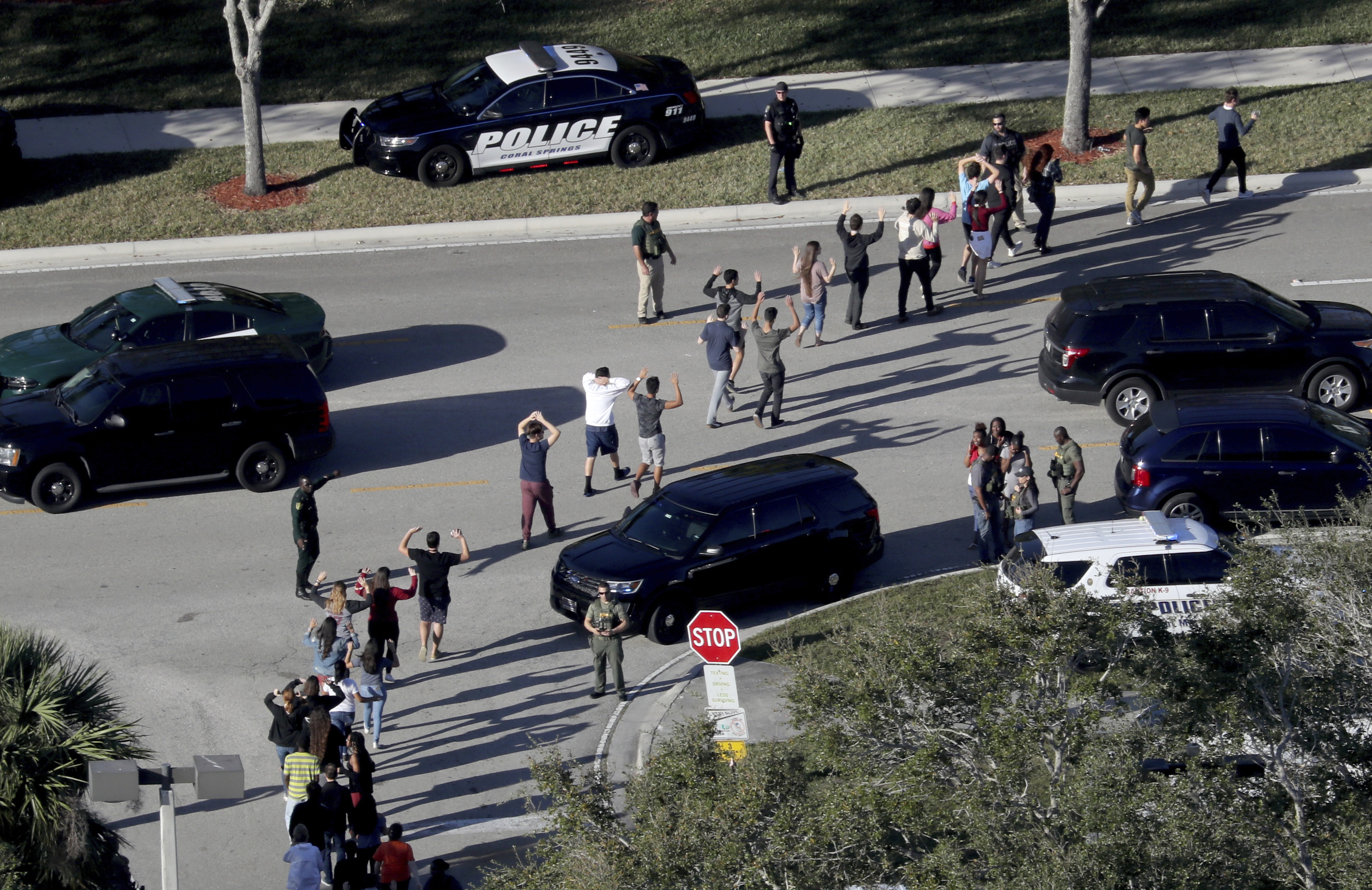 Students hold their hands in the air as they are evacuated by police from Marjory Stoneman Douglas High School in Parkland, Fla. on Feb. 14, 2018.