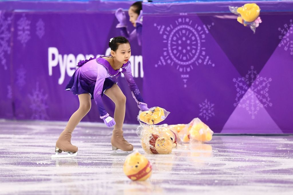 Flower girls collect Winnie the Pooh teddy bears thrown by supporters of Japan's Yuzuru Hanyu before he competed in the men's single skating short program of the figure skating event during the Pyeongchang 2018 Winter Olympic Games at the Gangneung Ice Arena in Gangneung on February 16, 2018.