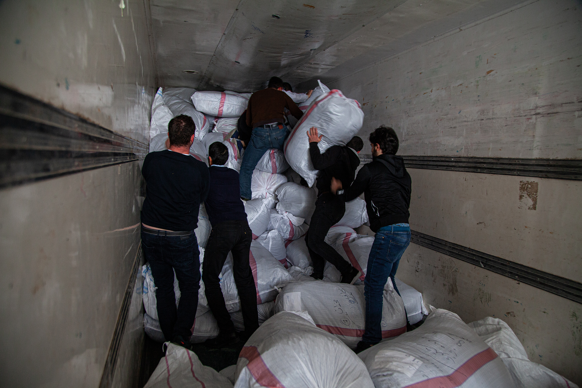 Men load sacks of humanitarian items into a truck in Gaziantep, Turkey, on Jan. 5, 2020. The aid was collected for newly displaced Syrians from Idlib.