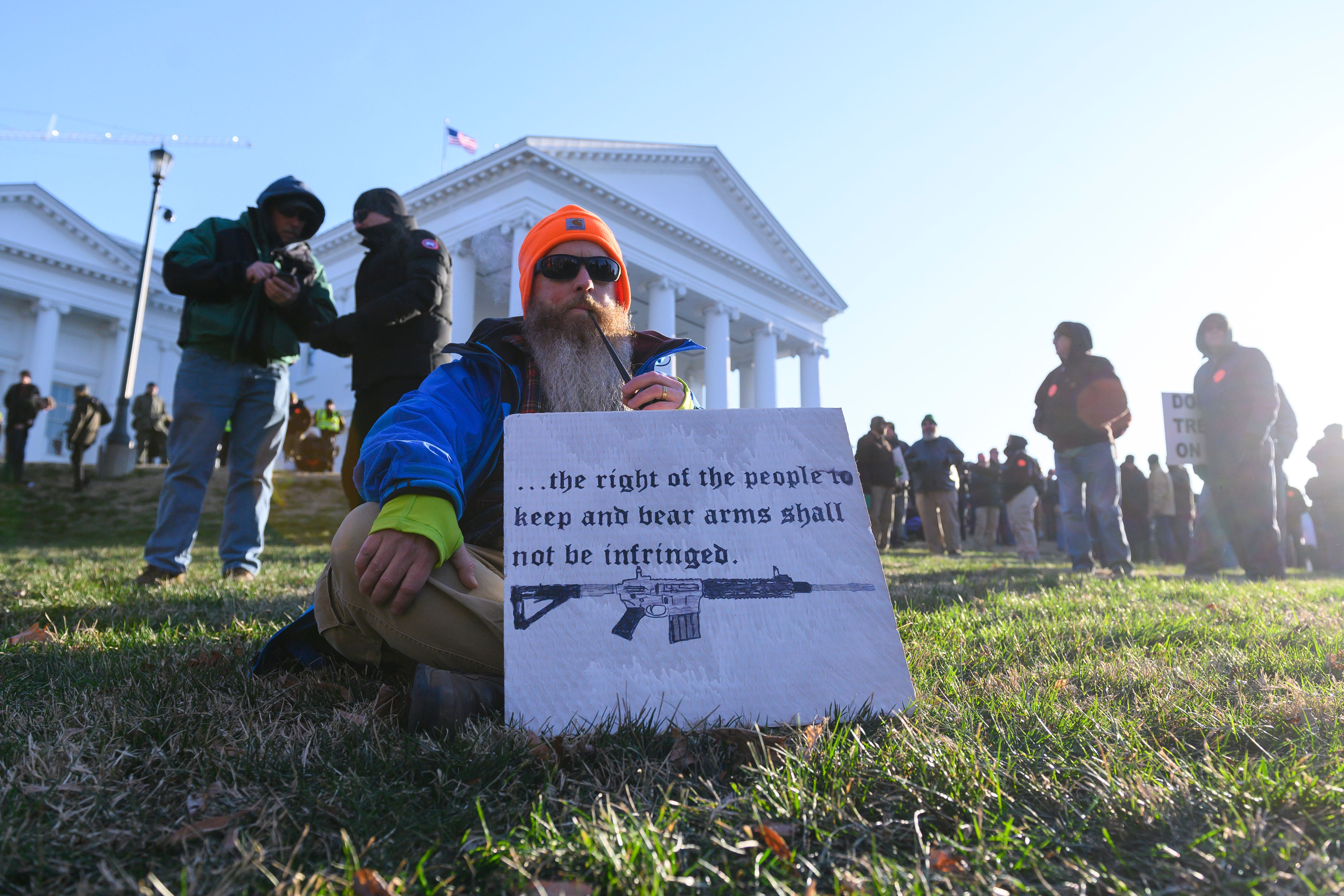 A pro-gun supporter smokes a pipe while displaying a sign as he waits for a rally to begin on the grounds of the Virginia State Capitol grounds in Richmond, Virginia on Jan. 20, 2020.