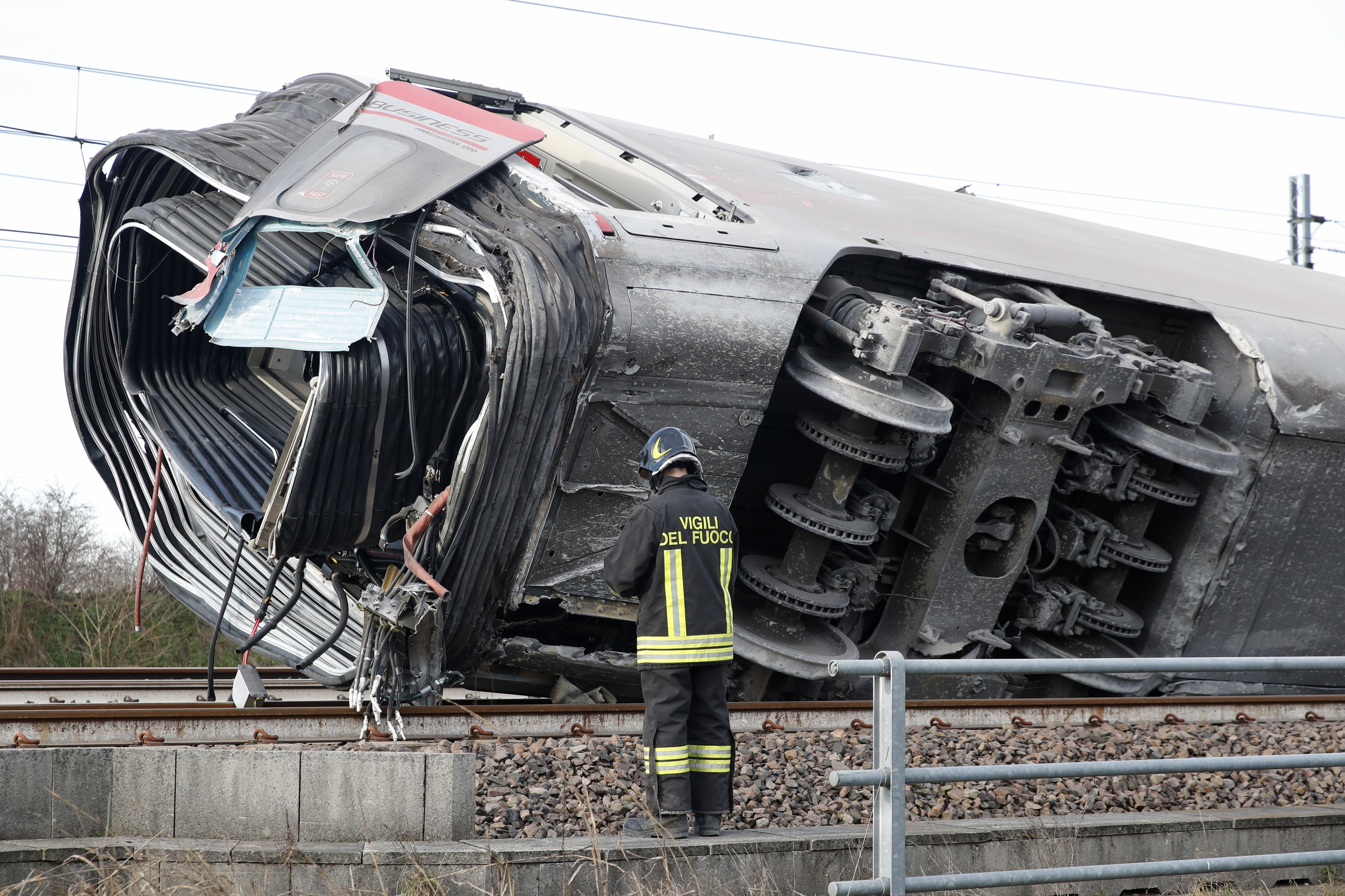 A firefighter inspects a derailed train carriage, near Lodi, northern Italy on Feb. 6, 2020.
