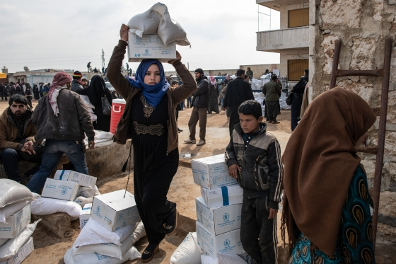 A displaced woman carries a box of humanitarian aid supplied by an NGO in Idlib, Syria, on Feb. 19, 2020.