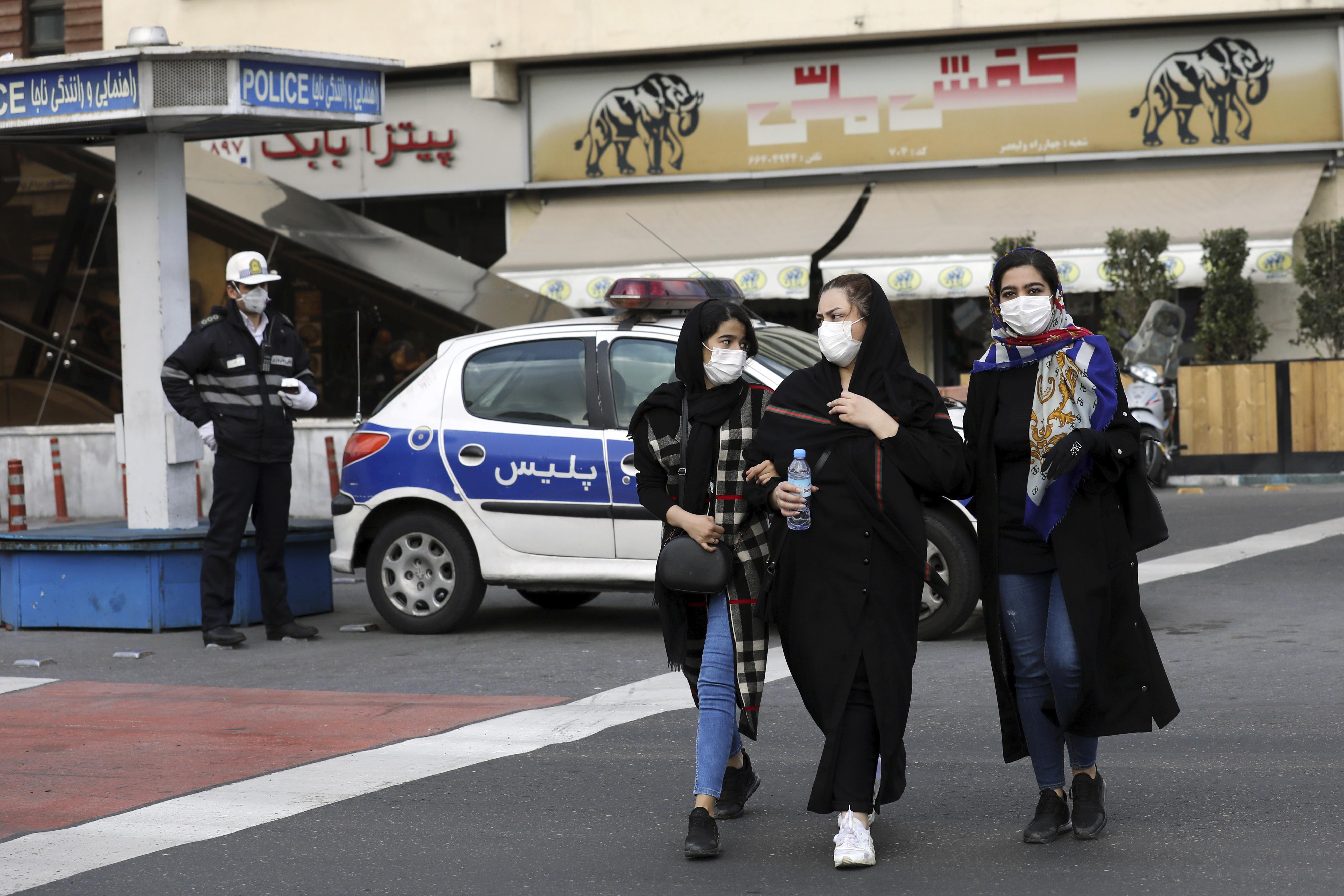 A policeman and pedestrians wear masks in Tehran, Iran, on Feb. 23, 2020.