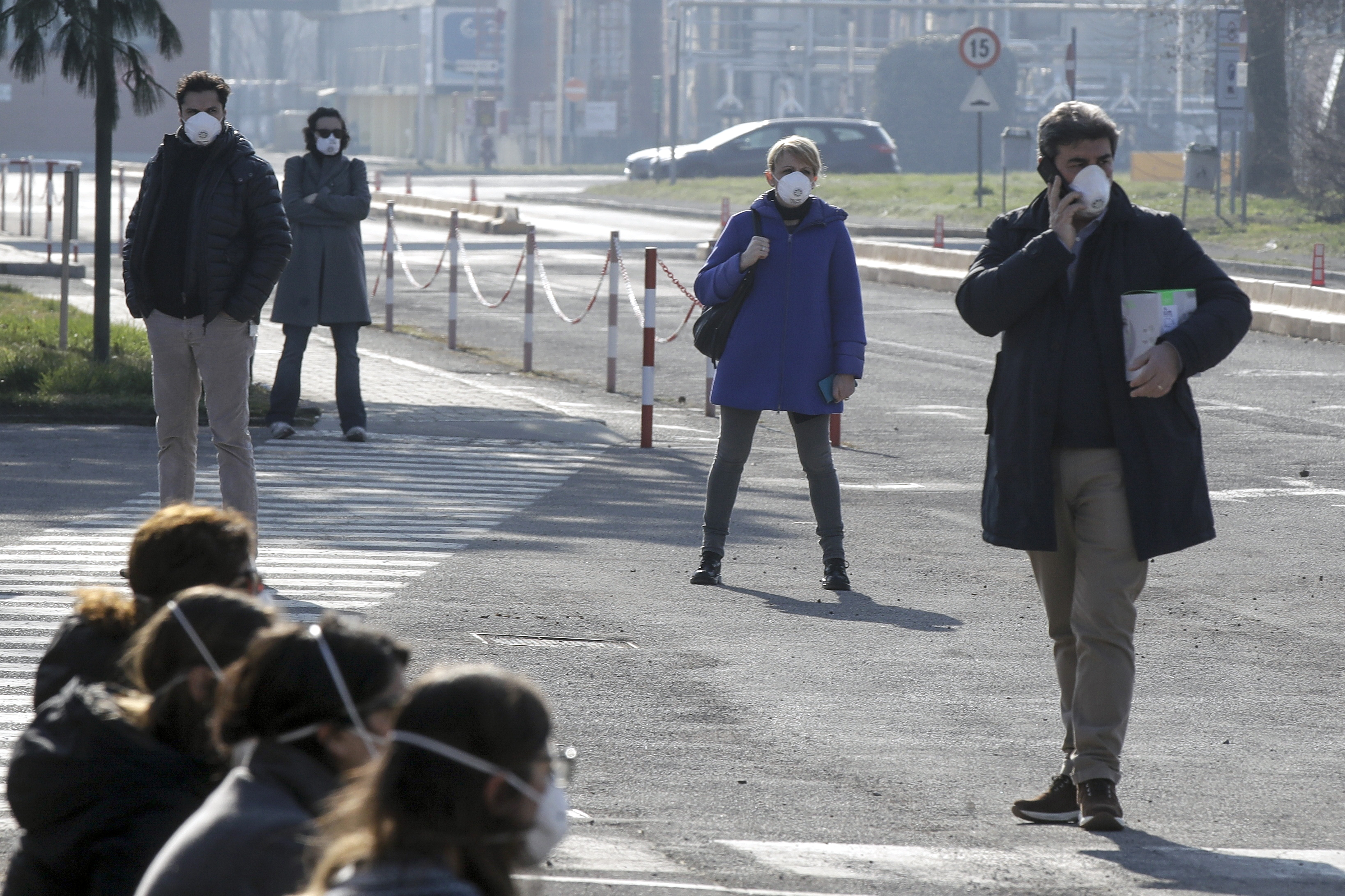 Workers wear masks at the Unilever factory where a 38-year-old working in the research and development branch fall ill with the new virus from China, in Casalpusterlengo, Northern Italy, on Feb. 22, 2020.