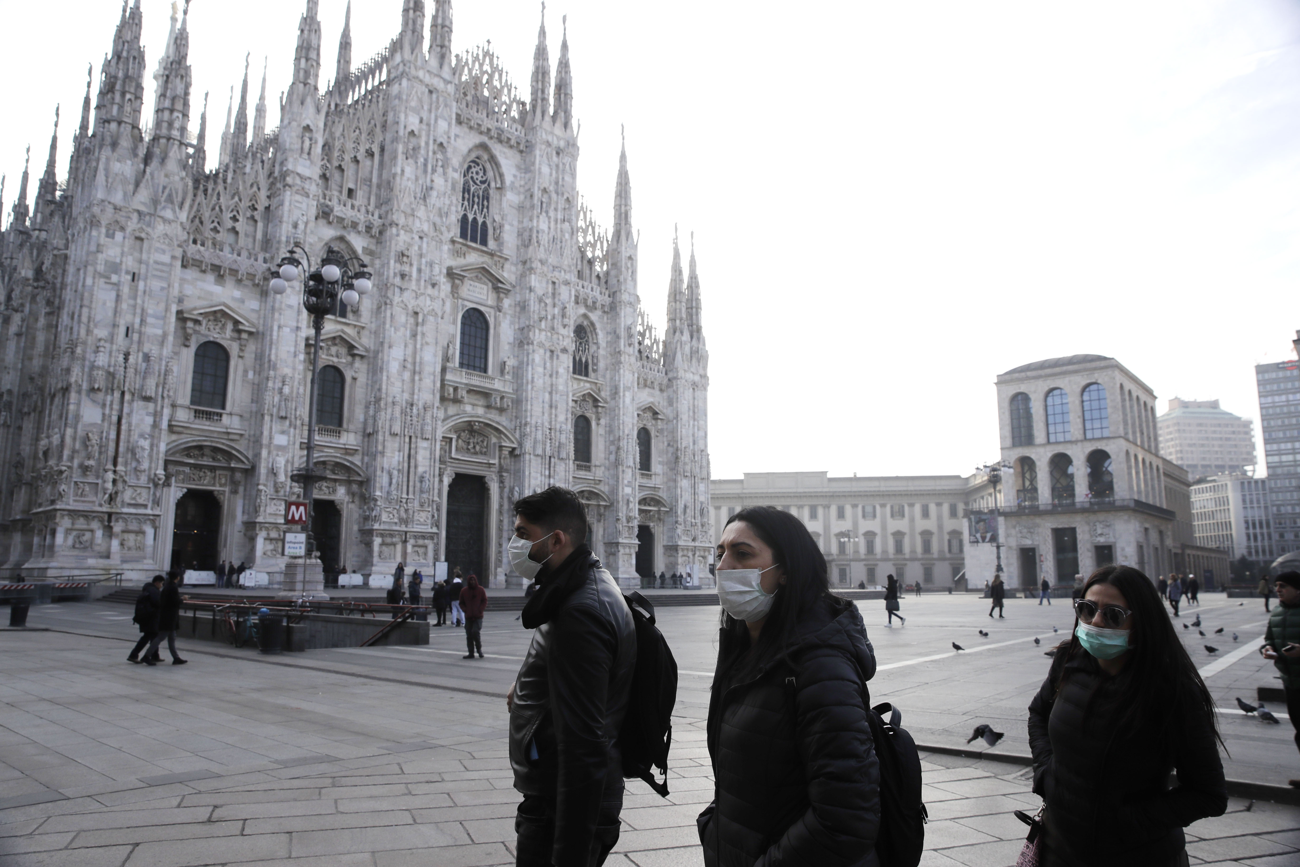People wearing sanitary masks walk past the Duomo gothic cathedral in Milan, Italy, on Feb. 23, 2020.