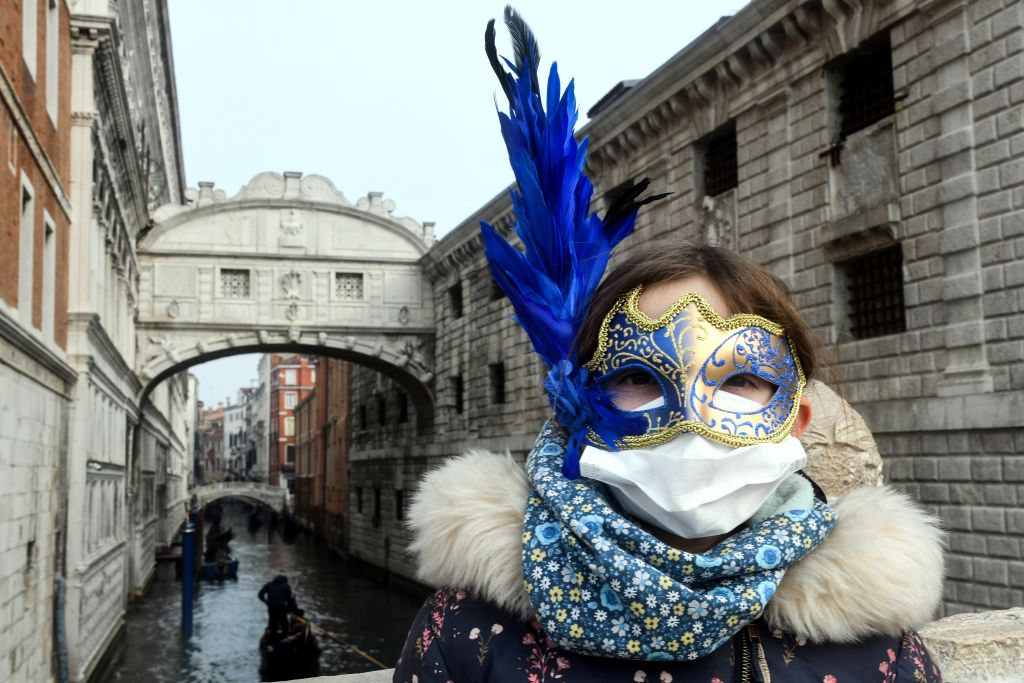 A young tourist joining in on carnival festivities wears a facemask in Venice, Italy, on Feb. 24, 2020.
