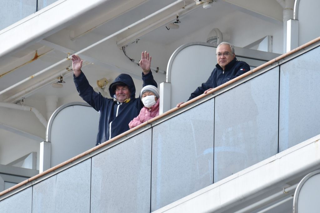 Passengers aboard the Diamond Princess cruise ship wave to reports in Yokohama, Japan, on Feb. 6, 2020.