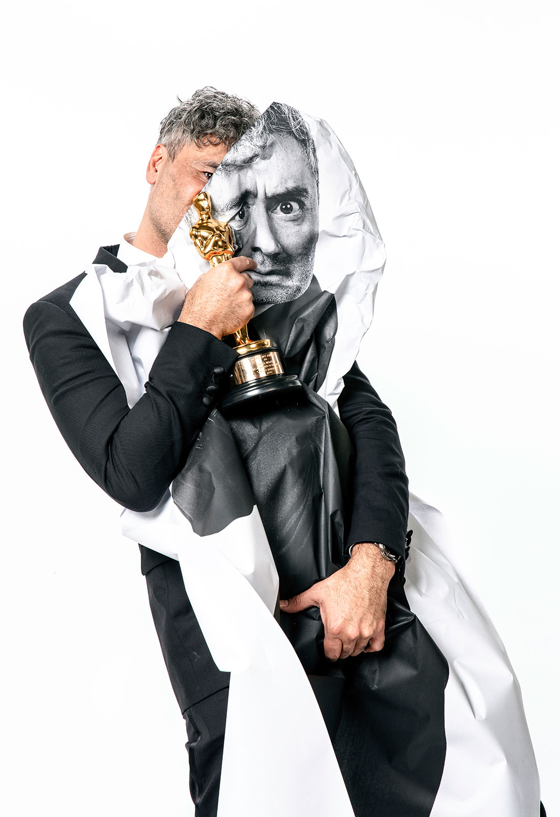 Taika Waititi poses with his Oscar for Best Adapted Screenplay.