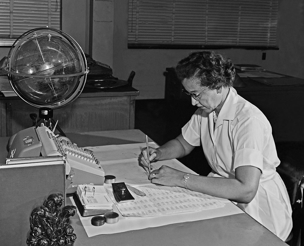 NASA space scientist and mathematician Katherine Johnson poses for a portrait at her desk with an adding machine and a 'Celestial Training device' at NASA Langley Research Center in 1962 in Hampton, Virginia.