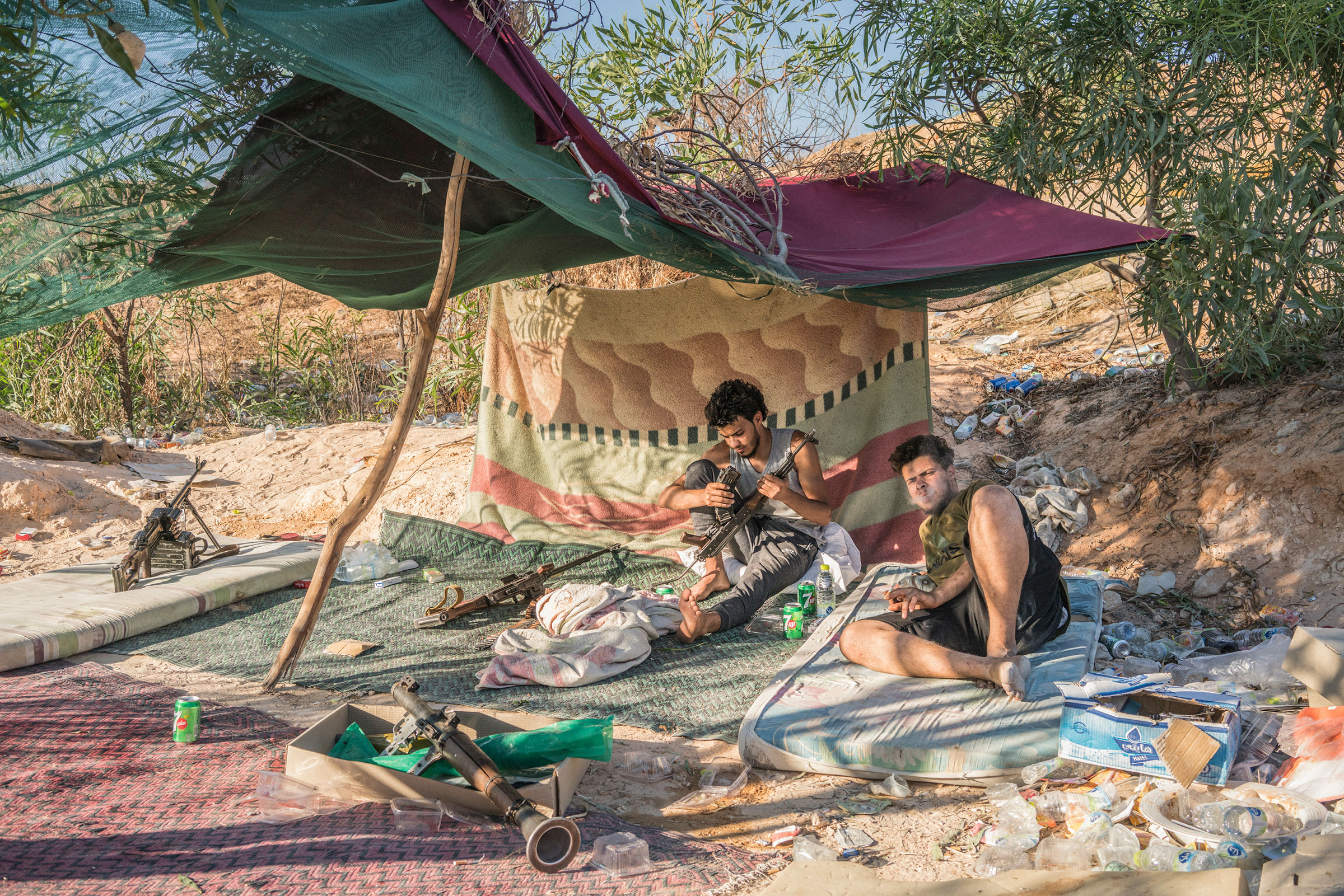Fighters loyal to the GNA sit under a makeshift tent on the international airport front line in Tripoli on July 4, 2019.