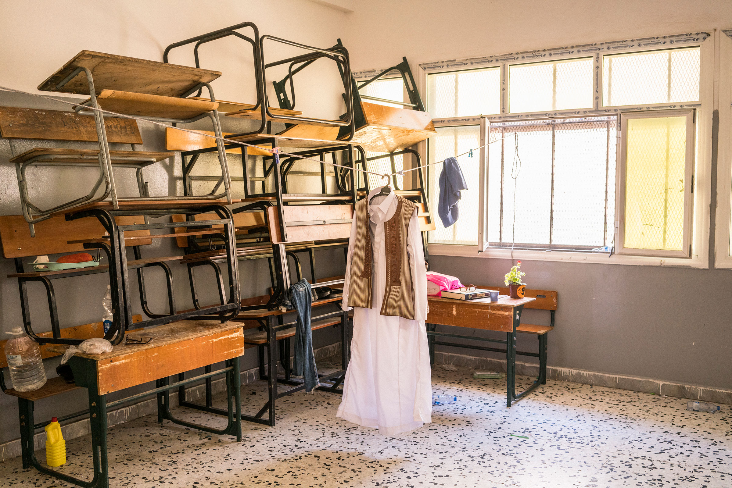 Clothes hang inside a school, which became a shelter for those fleeing their homes, on the front line in Tripoli.