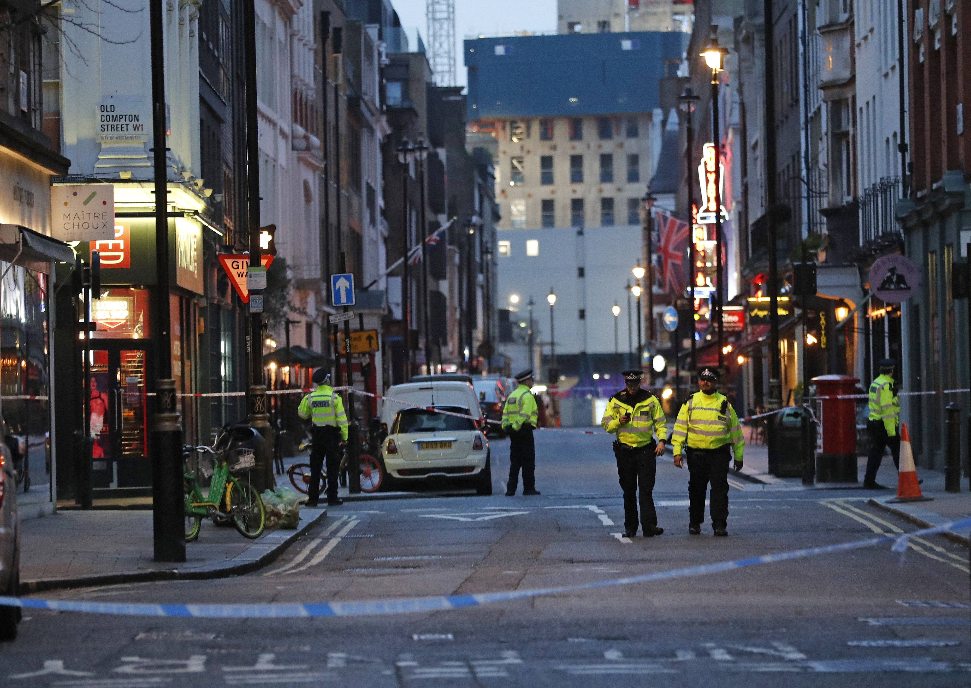 Police officers walk in a blocked a street in the Soho area of London after what's thought to be an unexploded World War II bomb was dug up at a construction site Monday Feb. 3, 2020. An area covering several blocs of the tightly packed neighborhood was cordoned off while police assessed the device.