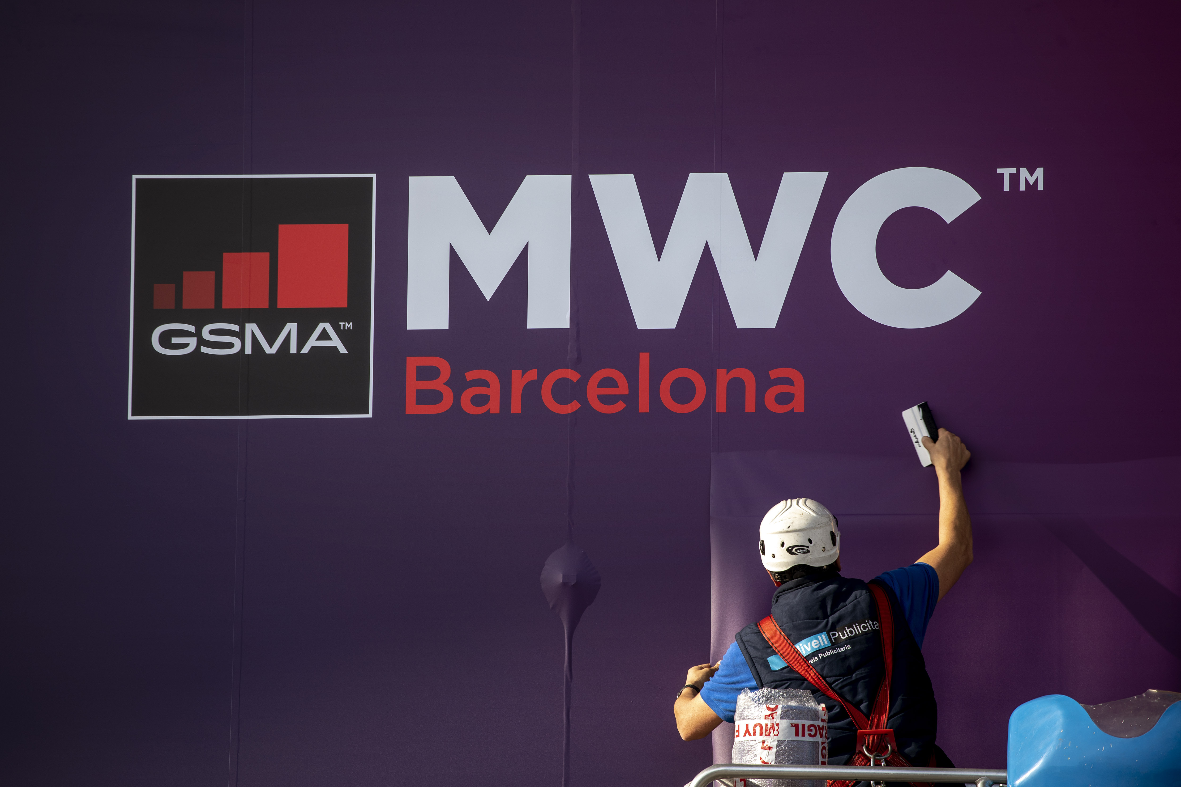 A worker fixes a poster announcing the Mobile World Congress 2020 in a conference venue in Barcelona, Spain on Feb. 11, 2020.