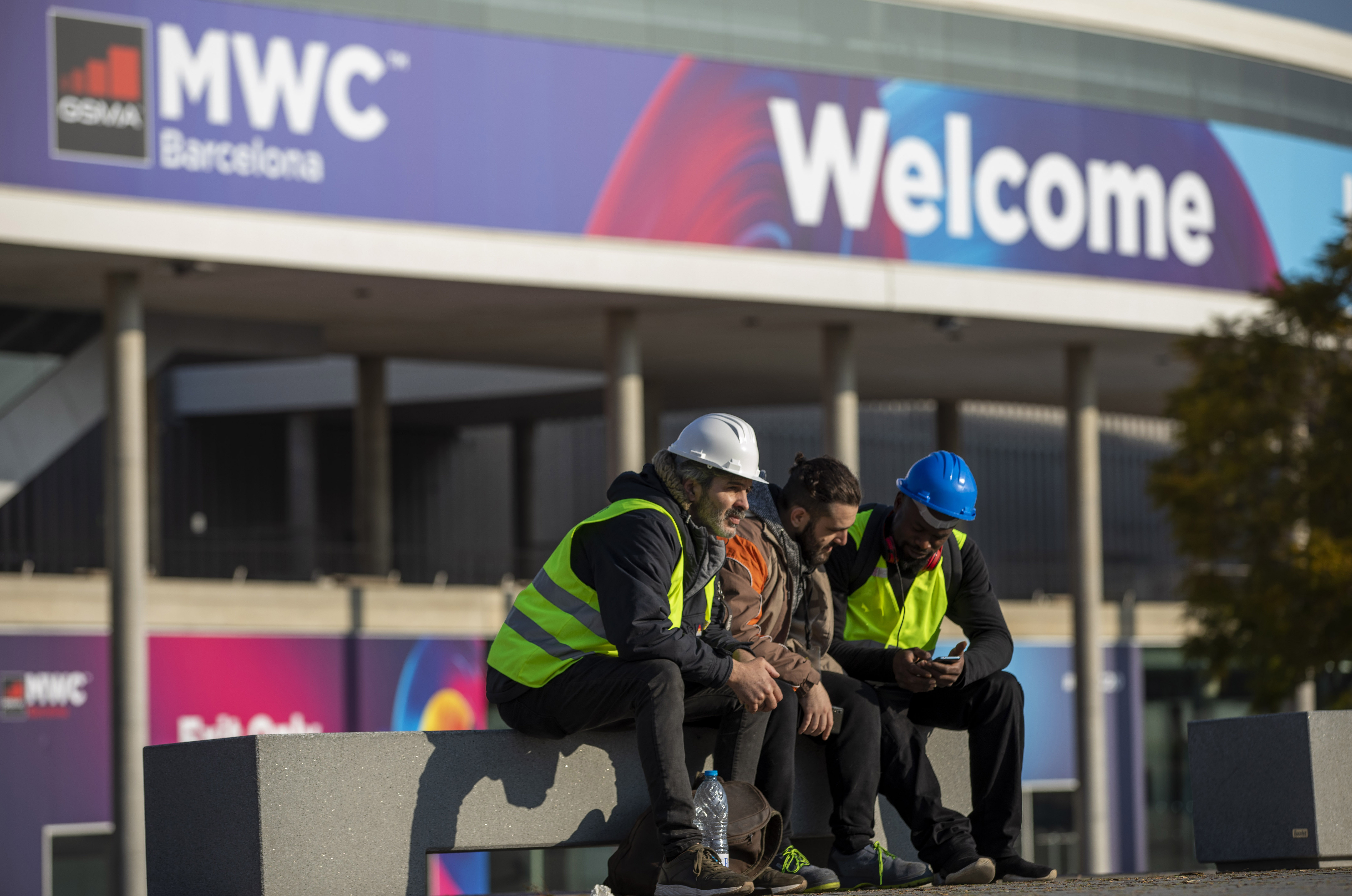 Workers at the Mobile World Congress sit outside the venue in Barcelona, Spain, Thursday, Feb. 13, 2020.