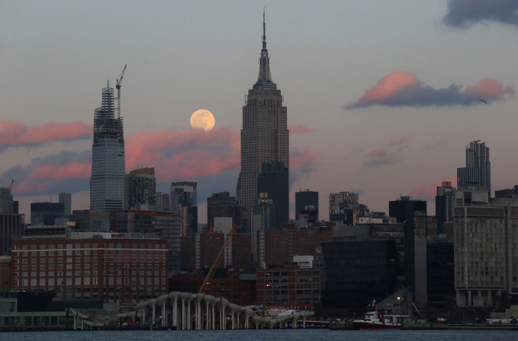 The Snow Moon rises next to the Empire State Building as the sun sets in New York City on February 8, 2020 as seen from Hoboken, N.J.