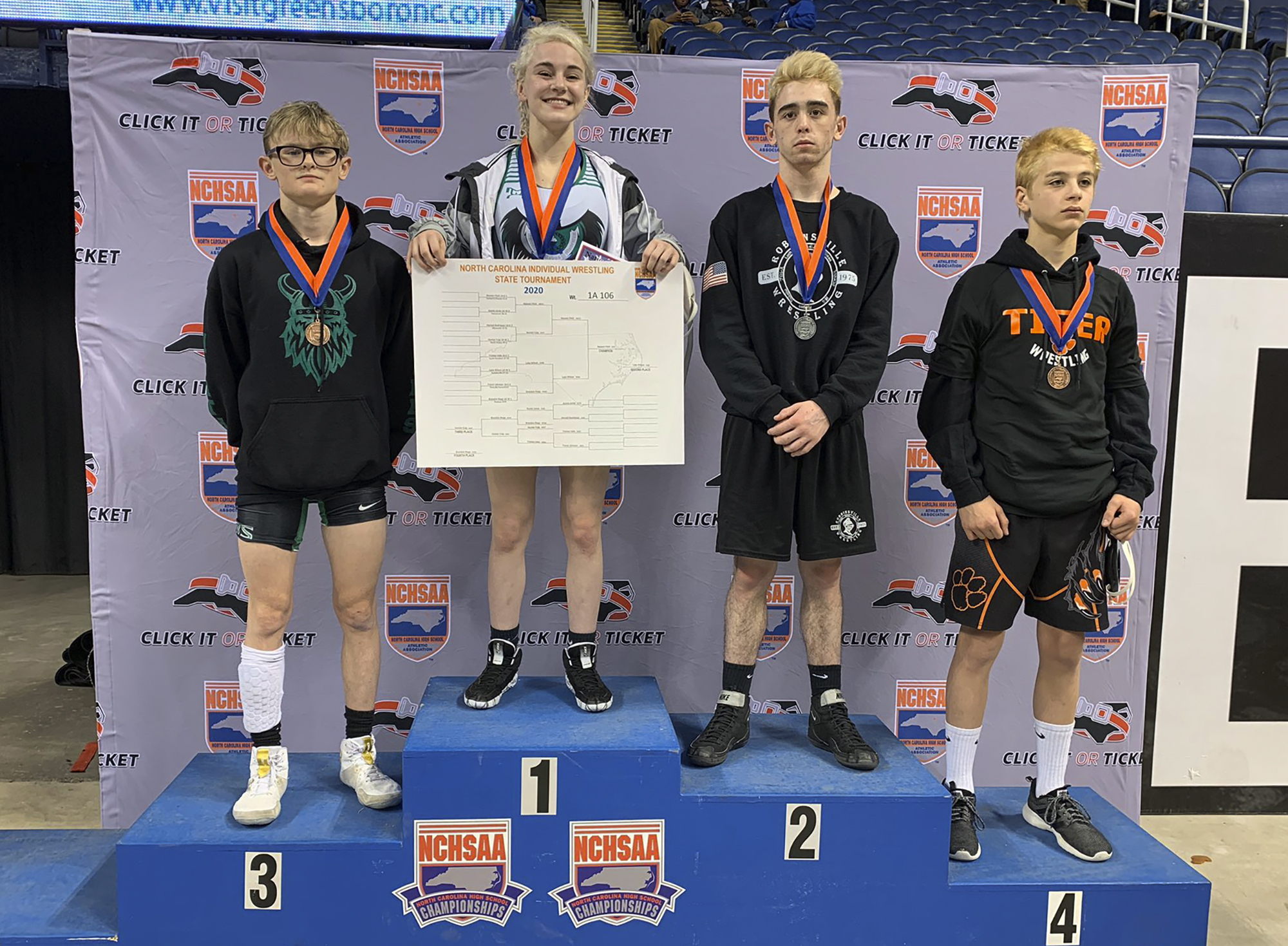 This photo provided by North Carolina High School Athletic Association (NCHSAA) shows Heaven Fitch, center, Luke Wilson, left, and Hunter Fulp, right, and Brandon Ropp, far right,  after the state wrestling championships in Greensboro, N.C, on Saturday, Feb. 22, 2020.